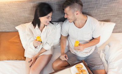 'Breakfast in bed' concept. Directly above shot of a beautiful young love couple lying in bed, enjoying a carefree weekend morning together. Wooden tray with breakfast on it in front of them.