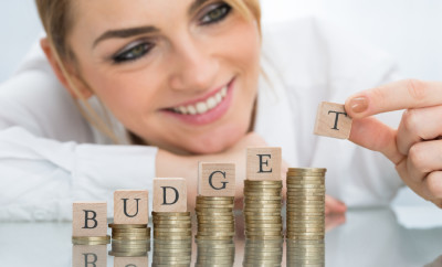 Close-up Of Happy Businesswoman With Budget Wooden Blocks On Stacked Coins