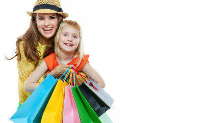Colourful vibes of family shopping. Portrait of happy mother hugging daughter with shopping bags on white background
