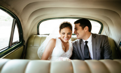 A beautiful Hispanic newlywed couple laughing in the backseat of a classic car in Havana Cuba.
