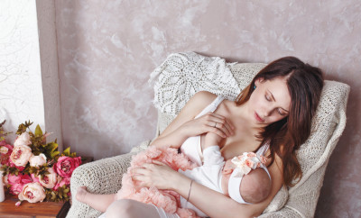 Happy young family, a mother breastfeeds little daughter. The concept of happiness of motherhood.