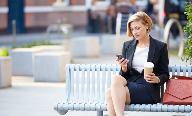Businesswoman On Park Bench With Coffee Using Mobile Phone