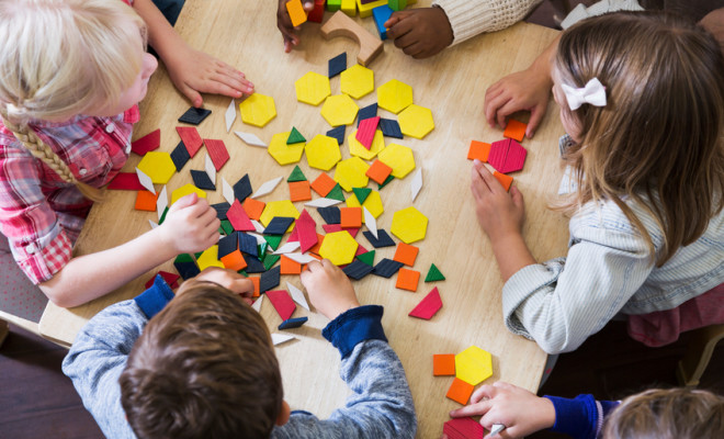 An overhead view of a group of five preschoolers sitting at a table playing with colorful blocks and geometric shapes.  They are unrecognizable since we see the tops of their heads and their hands.  They are in a preschool or kindergarden classroom.