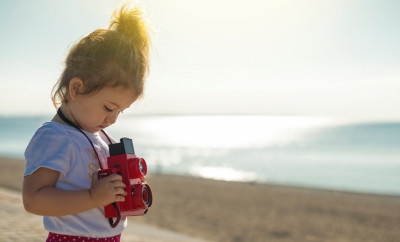 Cute little toddler taking pictures with a vintage twin lens reflex camera on the beach. Focus on the girl, blurred background, selective focus