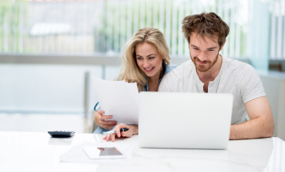 Young couple paying bills online using a laptop - home finances concepts