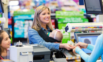 Mid adult Caucasian woman is smiling while shopping in grocery store. Mother is standing near elementary age daughter. She is wearing newborn baby girl in baby wearing wrap. Customer is handing cash to grocery store clerk, to purchase food from grocery store.