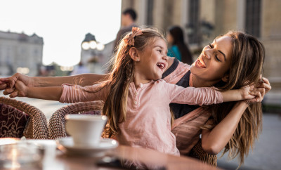 Cute little girl enjoying with her mother in a cafe.