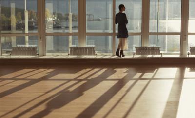 Woman standing near large window and looking to sunset. Big window, glass wall, warm room, sun and sea