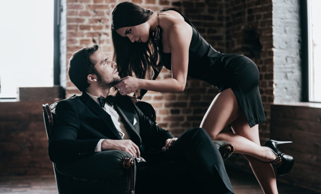 Beautiful young woman in cocktail dress leaning to her boyfriend sitting in chair while looking at each other in loft interior
