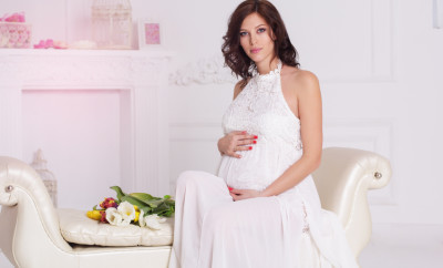 Beautiful pregnant woman is wearing white fashion sitting on white sofa