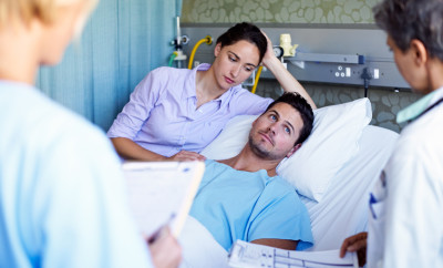 Shot of doctors talking to a men in a hospital bed while his wife looks wife