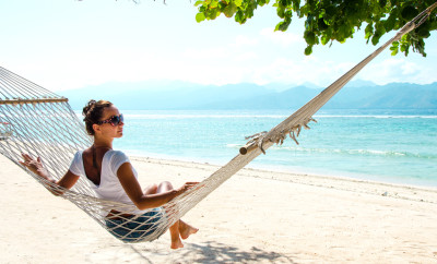 Girl relaxing in hammock on the beach near blue ocean. Bali, Indonesia. Stock image.