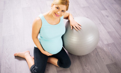 Pregnant woman resting on Fitness Ball.