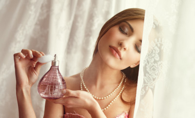 young woman applying perfume by the window