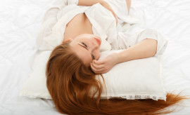 Portrait of a beautiful sexy girl lying on the back in bed in a man's shirt