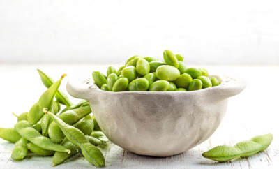 bowl of green beans on white wooden table