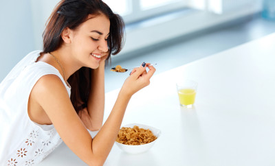 Beautiful young woman with a spoon in her hand and a bowl of cereal looking down and smiling. Healthy breakfast in the morning.