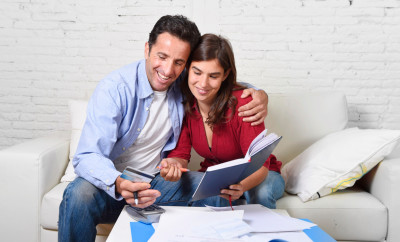 young attractive couple accounting at home couch with bank papers and documents, calculator and credit card living cost and mortgage expenses smiling happy in financial success and wealth