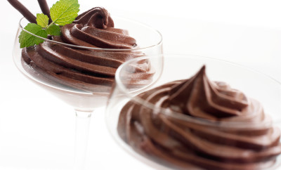 Chocolate Mousse dessert in a glass with mint on a white background.