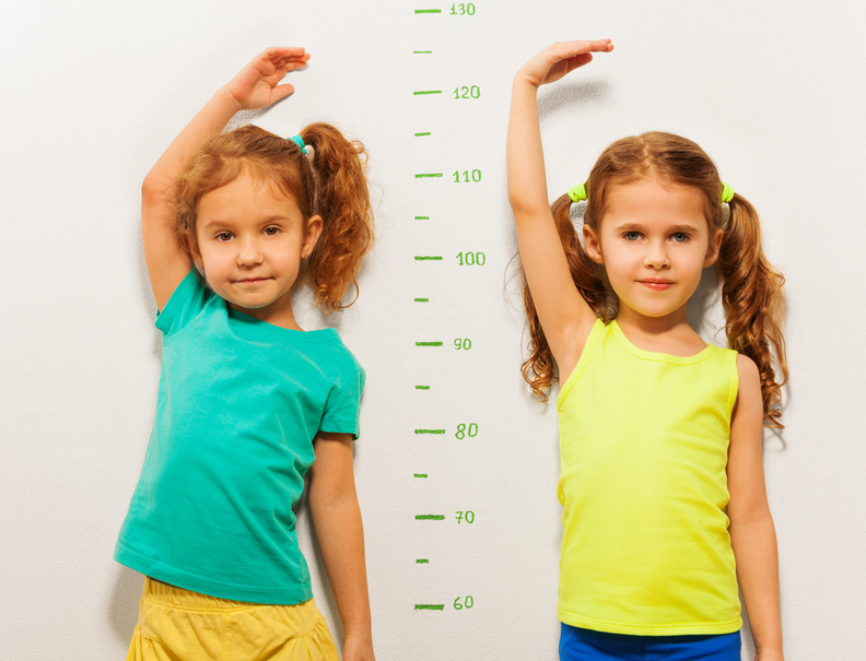 Two girls show height on wall scale at home
