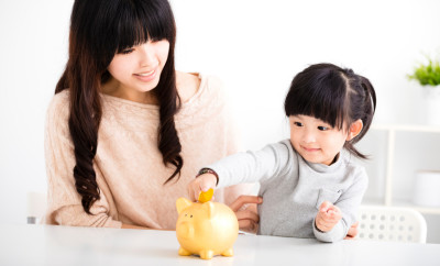 Happy mother and daughter Inserting Coin In Piggy bank..