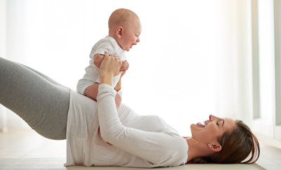 Shot of a young woman working out with her baby boy at home