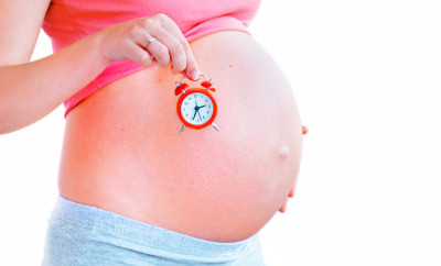 Pregnant woman holding an alarm-clock