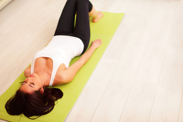 Young woman lying on the yoga mat