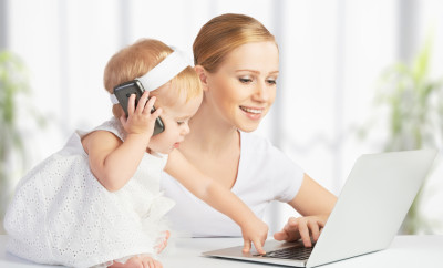 young mother with baby daughter works on the Internet with a computer and phone
