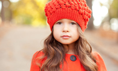 Beautiful baby girl 3-4 year old posing outdoors closeup. Wearing stylish hat and coat. Seasonal clothes. Childhood.