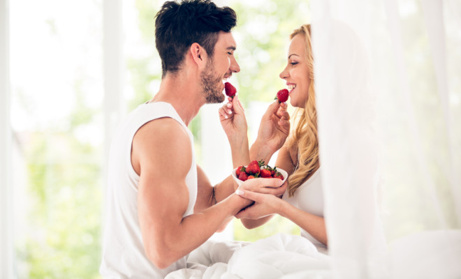 Man and woman eating strawberries in bed