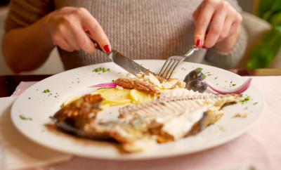 unrecognizable woman in restaurant eating fish,plate in front of her.