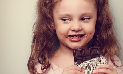 Curious cute kid girl eating dark chocolate and looking fun