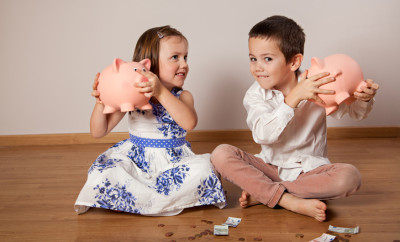 Children sitting on the floor and holding their piggy bank