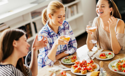 Picture of three smiling young women having some appetizers and white wine talking and laughing.