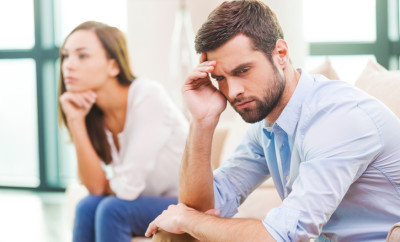 Depressed young man holding hand on head and looking away while woman sitting behind him on the couch