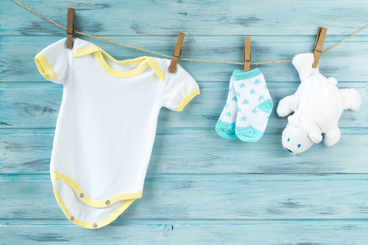 Baby clothes and white bear toy on a clothesline
