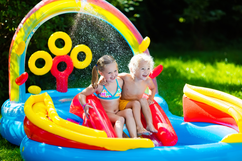 Kids siblings playing in inflatable swimming pool