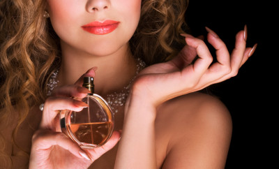 Beautiful woman applying perfume on her wrist