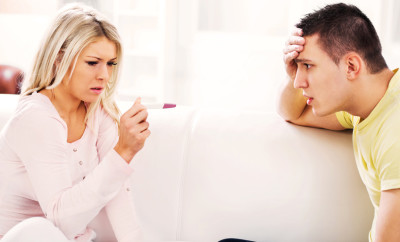 Young blonde woman is looking at a positive pregnancy test with a sad expression on her face.  Her boyfriend is holding his head in shock.