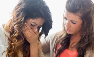 Woman crying with friend comforting her