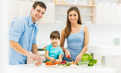 Parents with their daughter preparing food and looking at the camera.