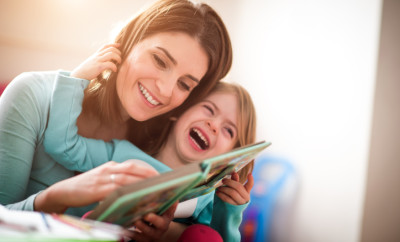 Mother and baby daughter at home reading a book and laughing together.