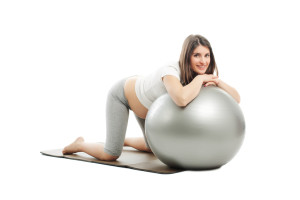 Young pregnant woman doing pilates