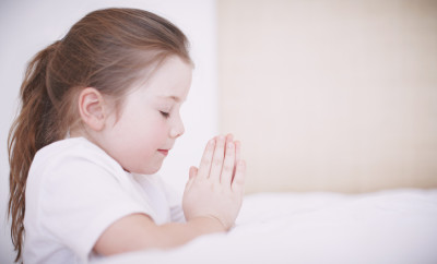 Side view of a young girl kneeling by her bed and saying her prayers