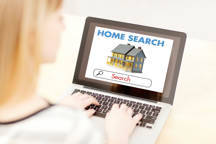 A young woman using her computer to search for home and real estate on the internet.