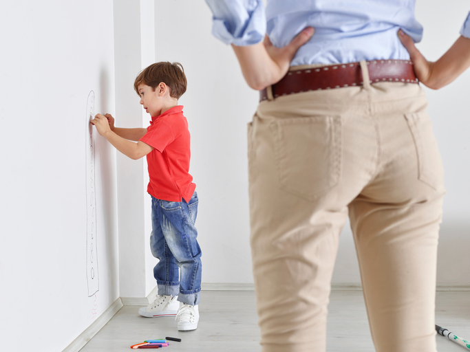 Little Boy Drawing On Wall With Crayons
