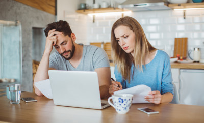 Young couple worried about their finances at home. They are wearing pajamas and drinking first coffee of the day at the kitchen.