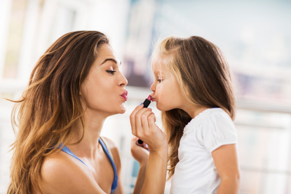 Young mother applying lipstick on her daughter.
