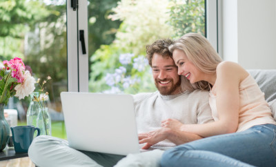 Happy young couple working online using a laptop at home - technology concepts